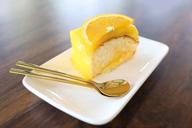 木製のテーブルの上の白い皿にオレンジのトッピングとオレンジのケーキ。