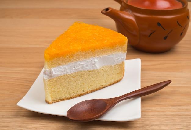 Апельсиновый торт с деревянной ложкой на фоне коричневого деревянного стола