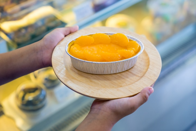 Orange cake on wooden plate in hand