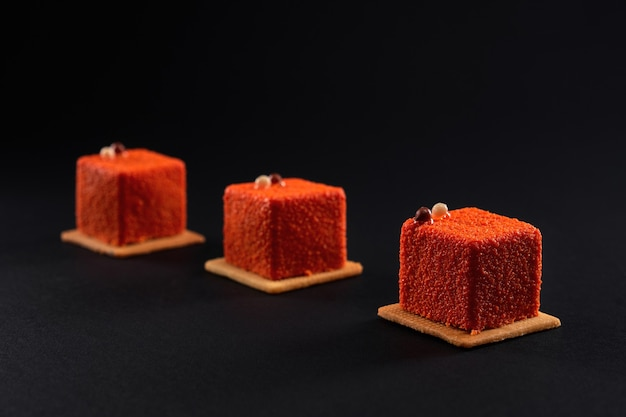 Orange cakes with matte surface isolated on black.