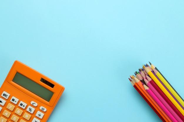 明るい青色の紙の背景にオレンジ色の電卓と色鉛筆。事務用品。教育。学校に戻る。上面図。テキストの場所。