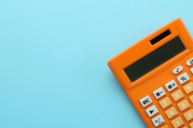 明るい青色の紙の背景にオレンジ色の電卓。事務用品。教育。学校に戻る。上面図。テキストの場所。