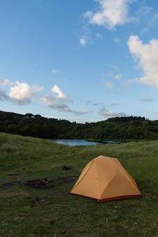 아름다운 풍경의 호수 옆에 있는 주황색 캠핑 텐트