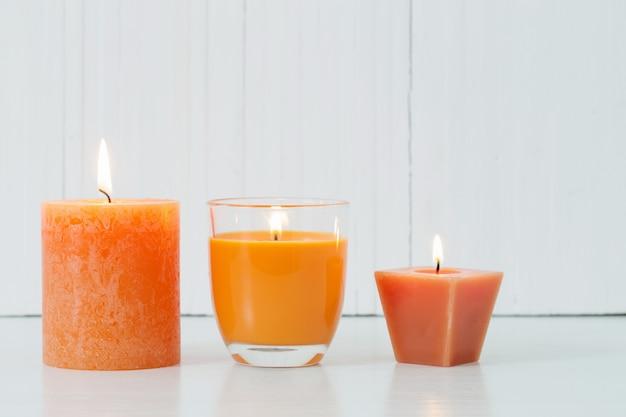 Orange candles on white background