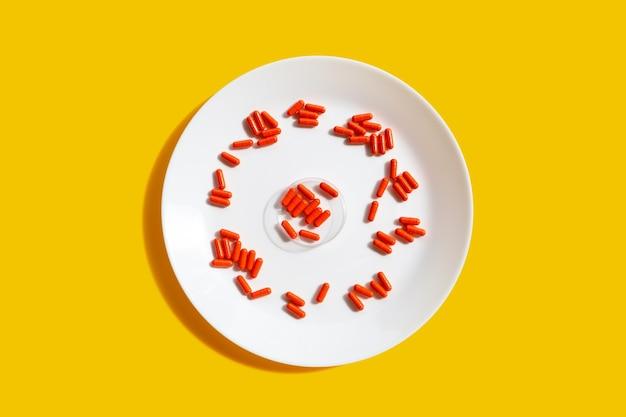 黄色の背景に白いプレートのオレンジ色のカプセルの丸薬。