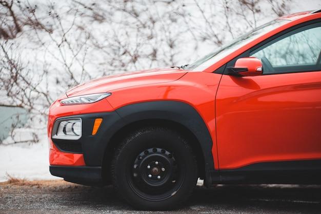 日中は雪に覆われた道路上のオレンジ色の車