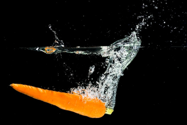 An orange carrot falling into water splash over black background