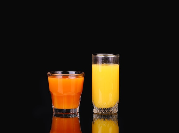 Orange and carrot juice on a black