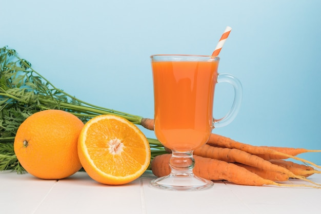 Orange and carrot smoothie, carrots and oranges on a white table. the concept of healthy eating.