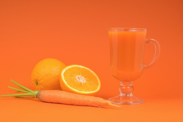 Orange and carrot smoothie in a glass glass on an orange background. the concept of healthy eating.