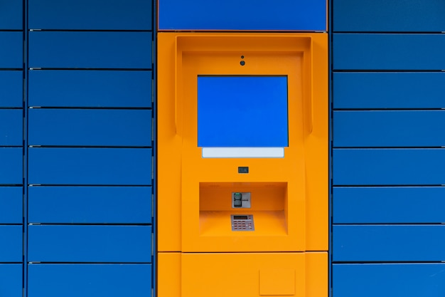 Orange cashpoint minibank with blank copyspace screen on blue panel tile background