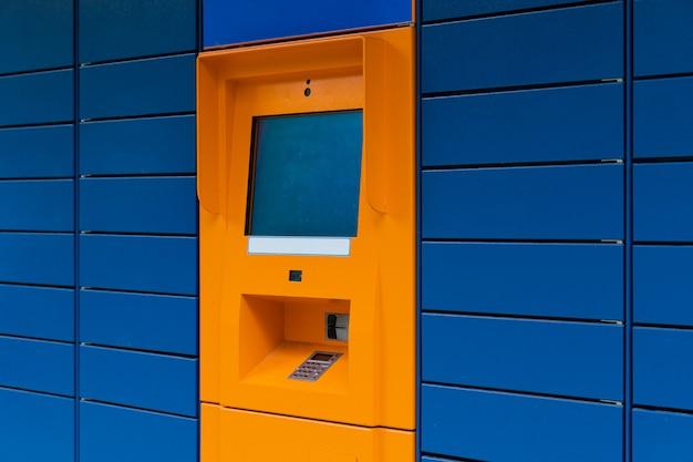 Мини-банк orange cashpoint с пустым экраном copyspace на синем фоне по диагонали