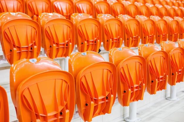 オレンジ色の椅子が屋根付きのスタジアムに並んでいます。ファンのためのトリビューン