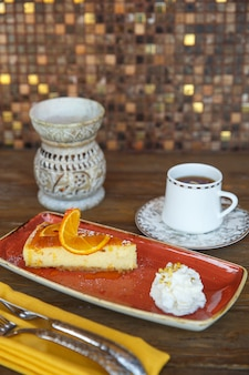 Orange cheese cake with cream, served with tea