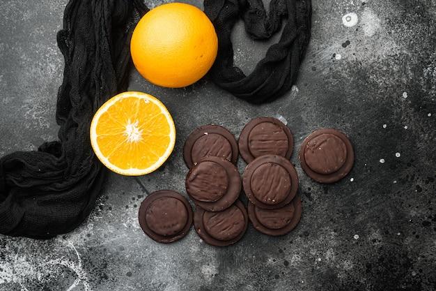 오렌지 초콜릿 코팅 비스킷 케이크 세트, 검은색 짙은 석재 테이블 배경, 위쪽 뷰 플랫 레이, 텍스트 복사 공간