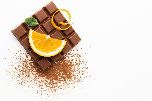 Orange and chocolate on plain background