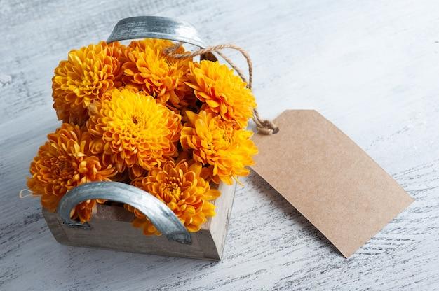 Оранжевые цветы хризантемы в деревянной коробке на деревенском столе. открытка с биркой