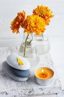Оранжевые цветы хризантемы с галькой и ароматической свечой на белом деревенском столе