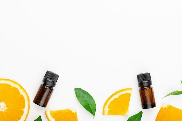 Эфирное масло апельсина цитрусовых, ломтики апельсина здоровых фруктов с зелеными листьями на белой рамке фона. ароматерапевтические масла, ароматические ванны, народная медицина. копирование пространства, вид сверху.
