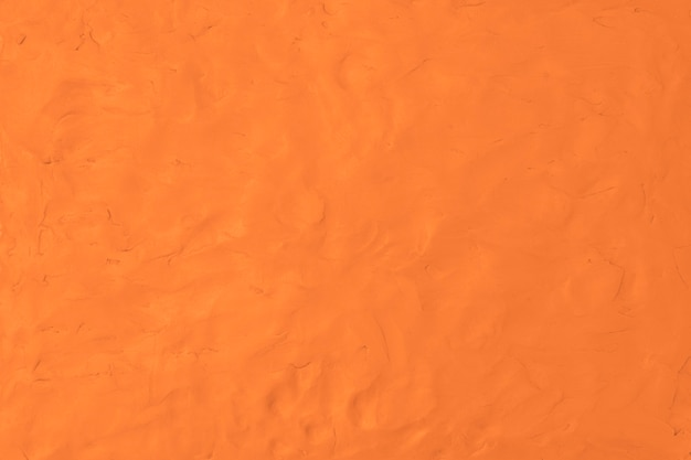 オレンジ色の粘土のテクスチャ背景カラフルな手作りの創造的な芸術の抽象的なスタイル
