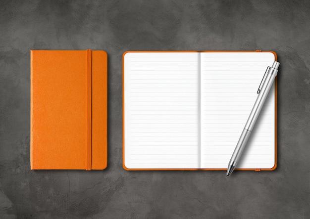 オレンジ色の閉じた状態と開いた状態のノートブックをペンで囲みます。暗いコンクリートのテーブルで隔離