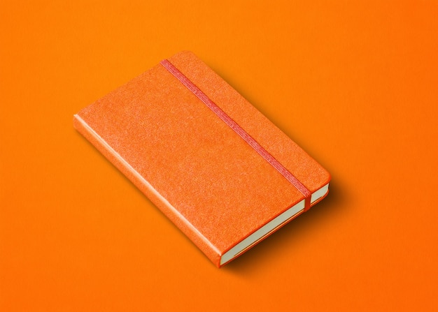 オレンジ色の閉じたノートブックのモックアップは、色の背景に分離