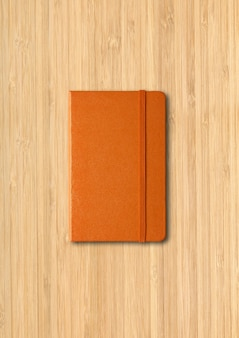 Orange closed notebook mockup isolated on wooden surface