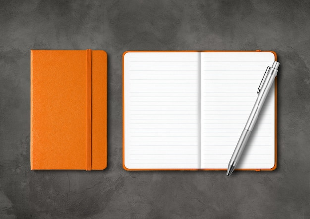 Orange closed and open lined notebooks with a pen. isolated on dark concrete table