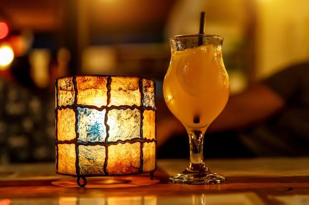 바에서 오렌지 칵테일. 튤립 모양의 유리와 램프