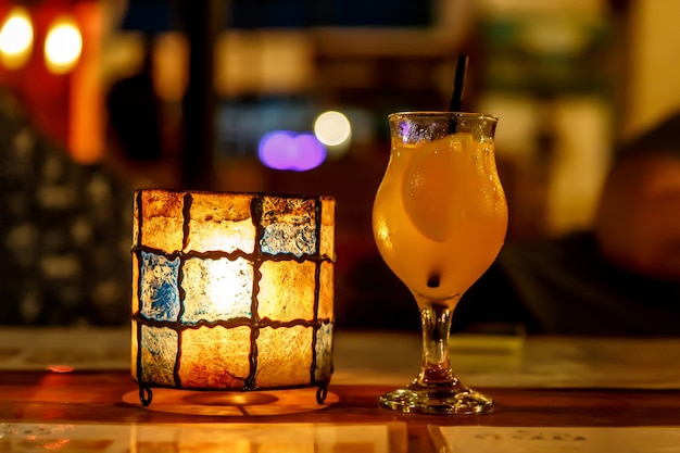 Orange cocktail at the bar. tulip-shaped glass and lamp