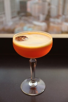 Orange cocktail drink on the rooftop terrace table with blurry urban view in background