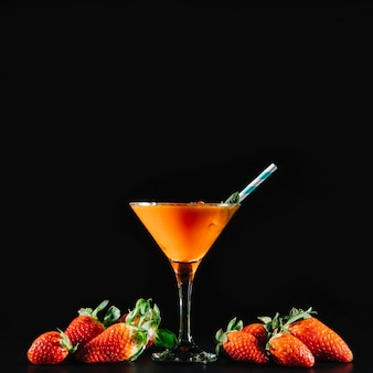 Orange cocktail and exotic fruits on black background
