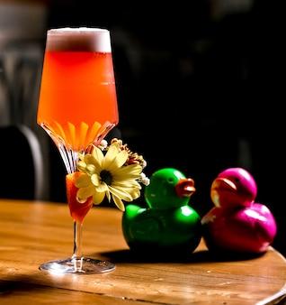 Апельсиновый коктейль, украшенный цветком рядом с хрустальными утками