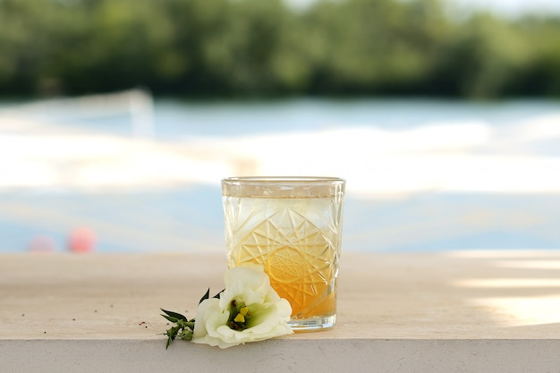 Orange cocktail in a glass. with flower decor