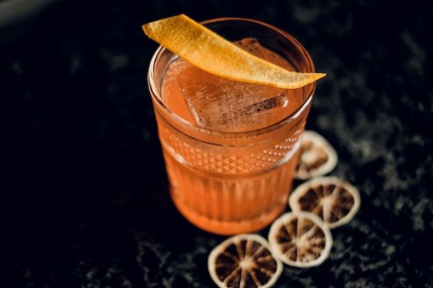 어두운 표면에 오렌지 칩과 얼음으로 아름다운 유리에 오렌지 칵테일