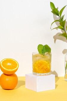 黄色の背景に、グラスの中のオレンジ色のカクテル、飲み物とグラスの横にあるカクテルシェーカー
