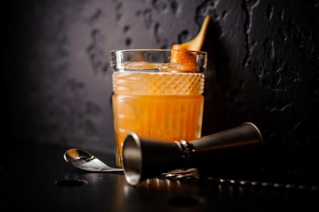 Апельсиновый коктейль из хрусталя с барной ложкой и джиггером
