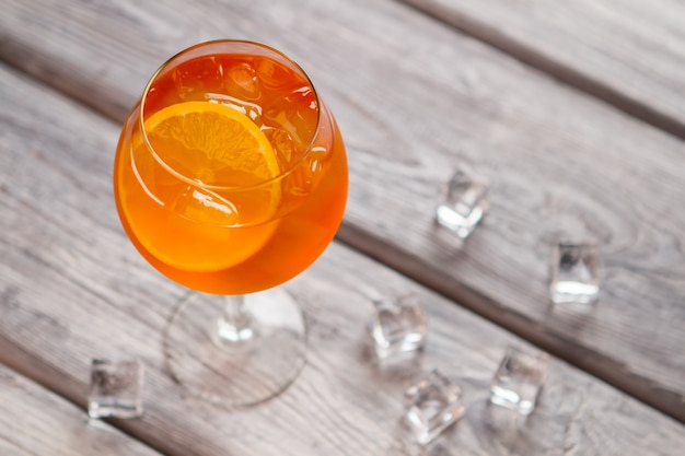 와인잔에 오렌지 칵테일입니다. 나무 배경에 얼음 조각입니다. aperol spritz의 입증된 레시피. 클럽에서 여가 시간을 보내고 있습니다.