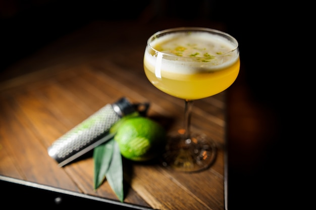 Orange cocktail and lime on dark table