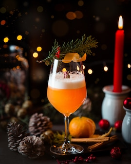 Orange cocktail with christmas cones, lights and red candle.