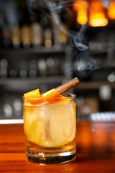 Orange cocktail with ice cube and orange zest. in the glass is a stick of cinnamon, from which there is smoke.