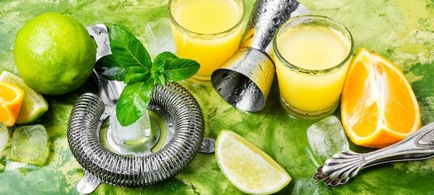 ライムスライスと氷とオレンジのカクテル。オレンジ色の飲み物のグラス