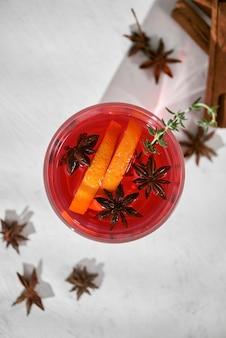 白いテーブルにラム酒、酒、洋ナシのスライス、ローズマリー、セレクティブフォーカスのオレンジカクテル