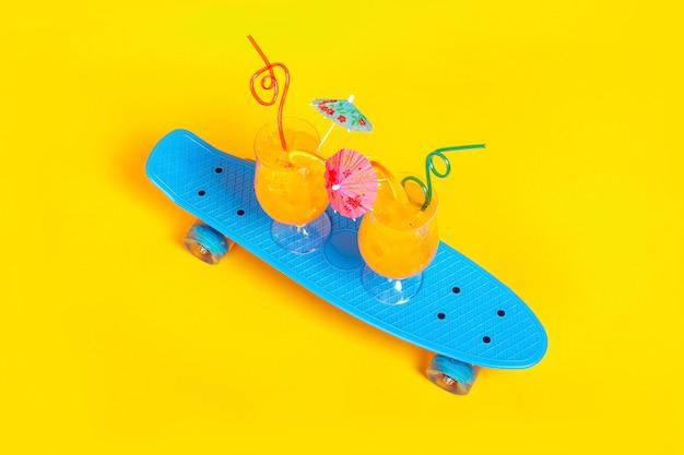 Апельсиновые коктейли на скейтборде на желтом