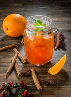 Orange coctail in the glass jar on wooden table with cinnamon
