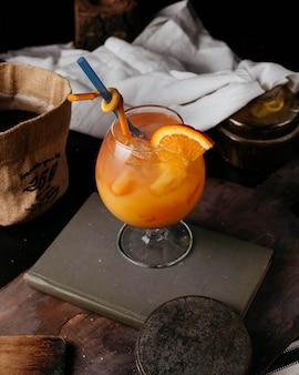 新鮮なオレンジジュースの氷と本のストローオレンジカクテル