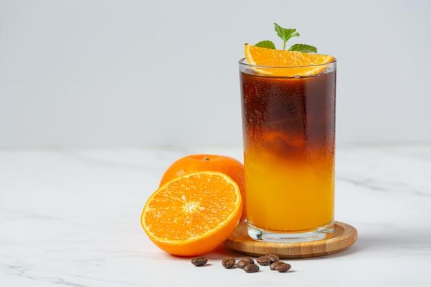 Cocktail di arancia e caffè sulla superficie bianca.