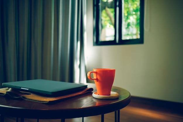 Оранжевая кофейная чашка и ноутбук на столе в кафе.