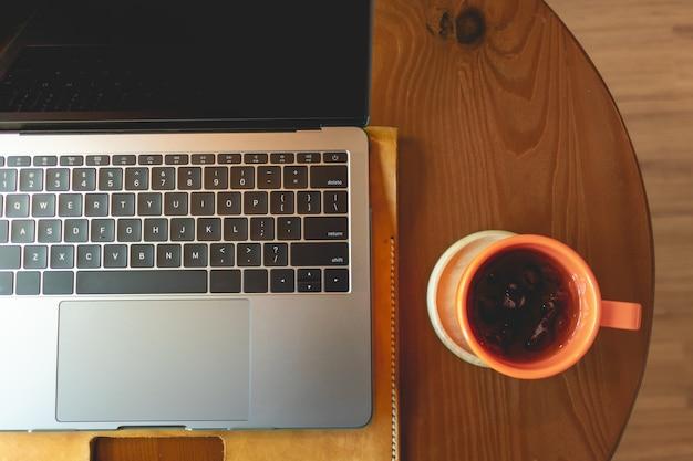 カフェのテーブルにオレンジ色のコーヒーカップとノートパソコン。