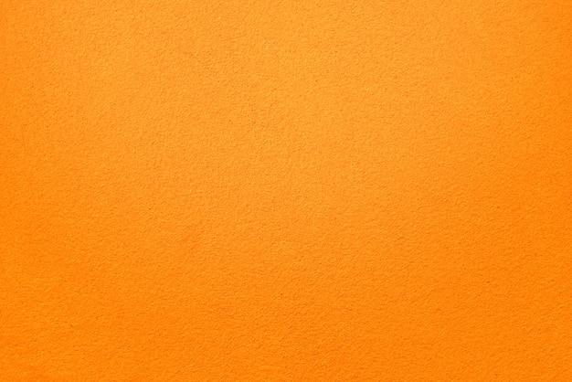 オレンジ色のコンクリートの壁のテクスチャの背景。細かく粗いコンクリート表面。